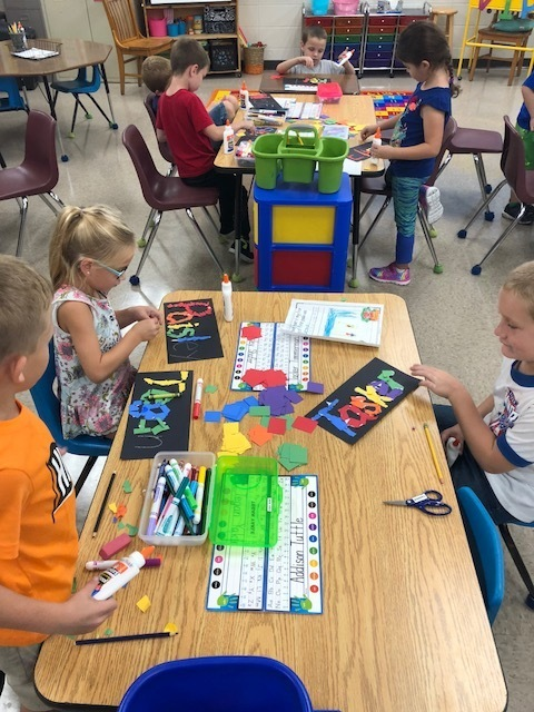 First Graders working on outlining their names to fit the theme of 1st Grade, You Are A Rainbow Of Possibilities!