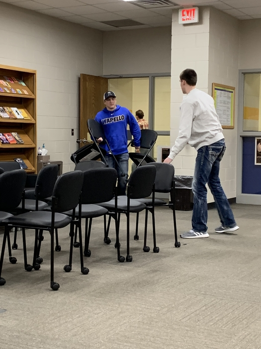 Students helping carry in furniture